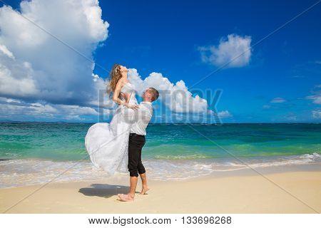 Happy bride and groom having fun on a tropical beach. Wedding and honeymoon on the tropical island.