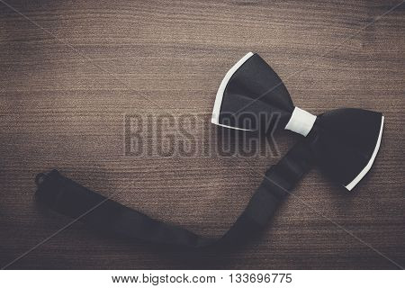 black and white bow tie on wooden table