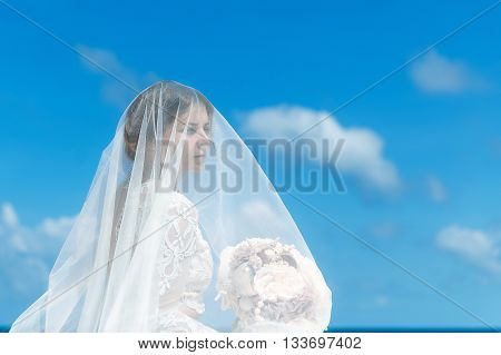 Beautiful brunette fiancee in white wedding dress with big long white train and with wedding bouquet stand on shore sea. Wedding and honeymoon concept.