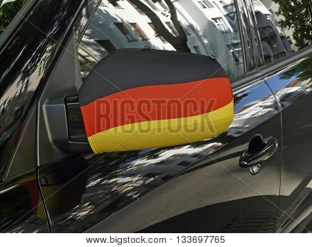 Outside mirror in black-red-and-gold the German national flag at the car of a soccer fan in Germany.