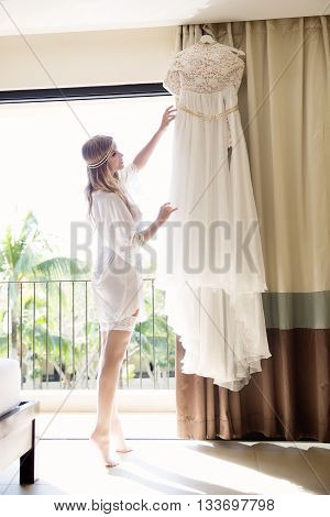 beautiful young bride with a white wedding dress. Last preparations for the wedding. Bride waits for her groom. Morning the bride.