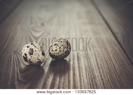 two quail eggs on the brown wooden table