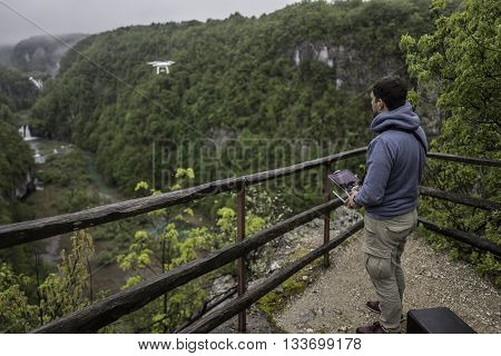 Man is operating the drone with a Plitvice waterfalls background