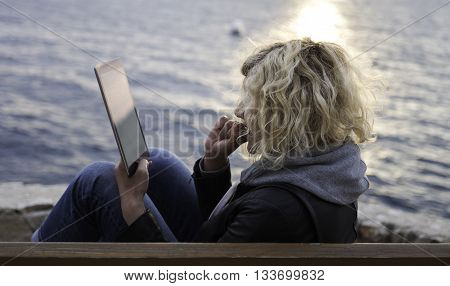 Blonde girl with curly hair is seating on the bench and absorbedly watching something in tablet