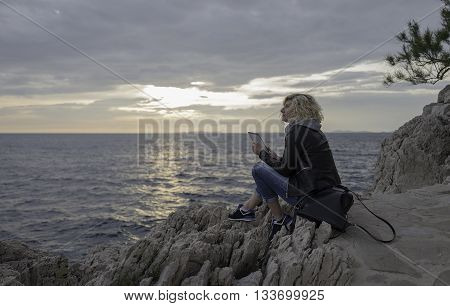 Beautiful blonde girl is seating on the stones near of the sea with tablet in hands and watching into the distance.