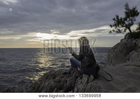 Beautiful blonde girl is seating on the stones near of the sea and watching the tablet