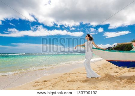 Beautiful brunette bride in white wedding dress with big long train having fun on shore sea. Tropical sea in the background. Summer vacation concept.