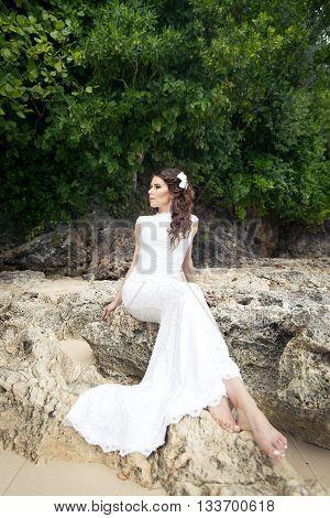 Beautiful bride on the rock. Wedding and honeymoon in tropics concept.
