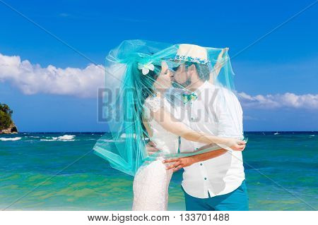 Beautiful brunette bride in white wedding dress with turquoise veil and groom having fun on shore sea. Tropical sea in the background. Summer vacation concept.