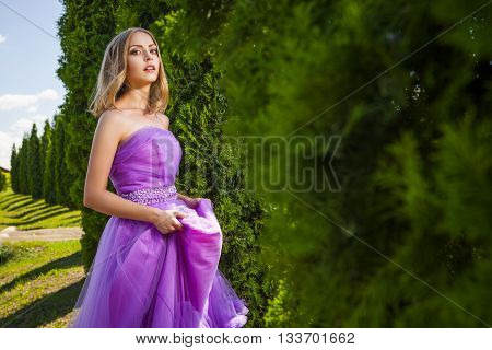 Portrait of blonde lady in violet dress looking at camera near green trees.Row of trees on background