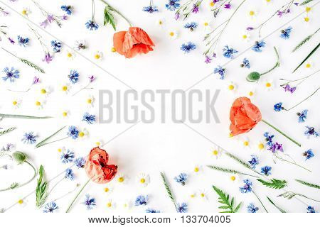floral frame with red poppies chamomile flowers cornflowers and green branches. Flat lay top view