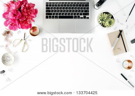 Workplace with laptop succulent peonies golden scissors spool with beige ribbon pencils and diary. Flat lay composition for bloggers magazines social media and artists. Top view.