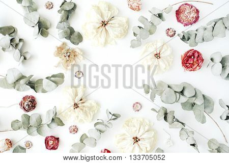 frame with red roses or ranunculus white tulips and green leaves on white background. Flat lay top view