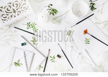 Workspace with notebook sketchbook brushes clean paper vintage casket pen candle and headphones. Flat lay overhead view. Artist working place