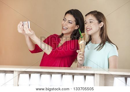Woman Taking Self Portrait With Daughter Holding Chocolate Ice Cream