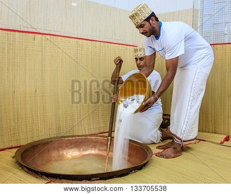 NIZWA, OMAN, MAY 27, 2016: factory worker pours sugar into a copper kettle for making of traditional Omani halwa