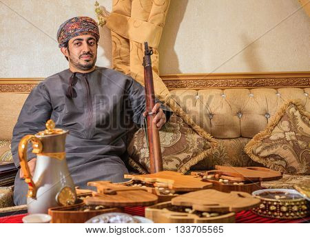 NIZWA, OMAN, MAY 27, 2016: Omani man with a rifle behind a table with traditional Omani sweets