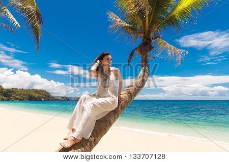 Young beautiful bride in white wedding dress on the palm tree on a tropical beach. Tropical sky and see in the background. Summer vacation concept.