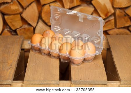 Dozen of brown eggs on brown wooden stand