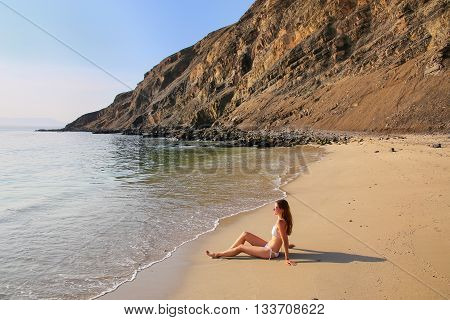 Young Woman In Bikini Sitting At La Mina Beach In Paracas National Reserve, Peru