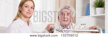 Care Assistant Helping Elderly Man