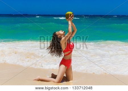 Young beautiful Asian girl with long black hair in red bikini drinking coconut water on the beach of a tropical island. Summer vacation concept.