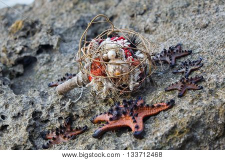 Wedding bridal bouquet made ​​of shells and pearls and other natural materials and sea stars on the rocks. Wedding and honeymoon in the tropics.