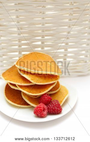 Small pancakes topped with berries isolated on white. Food background