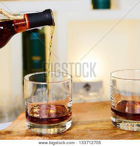 barman pouring whiskey in front of whiskey glass
