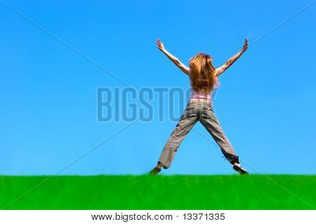 Happy young woman jumping under clean blue sky