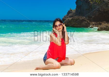 Young beautiful Asian girl on a tropical beach. Summer vacation concept.