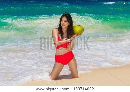 Young beautiful Asian girl in red cloth with coconut on the beach of a tropical island. Summer vacation concept.