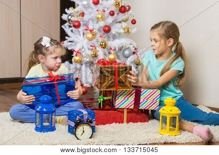 Two Girls Share Presented New Year Gifts At The Christmas Tree
