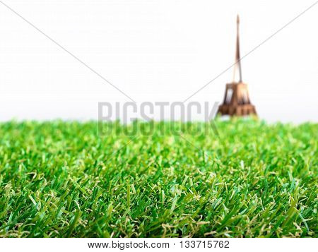Artificial grass with blurry background of Eiffel tower paper model