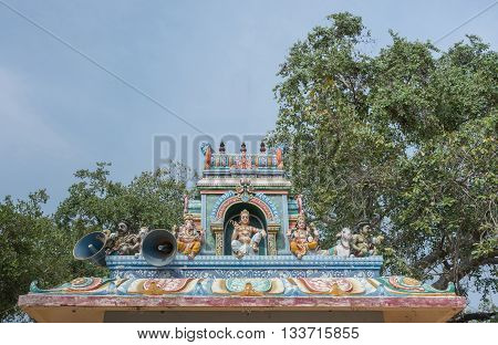 Chettinad India - October 17 2013: Kothamangalam Ayyanar horse shrine. On top of small shrine sits Lord Shiva and his two sons Ganesha and Murugan. Ayyanar figures on the corners with nandi the bull.