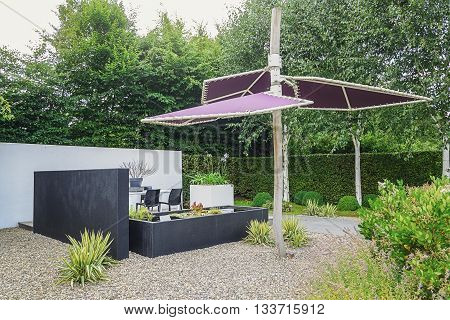 Appeltern The Netherlands July 22 2015: The Gardens of Appeltern is the inspiration garden park in the Netherlands. In this picture a garden with modern garden furniture trendy pond and parasol.