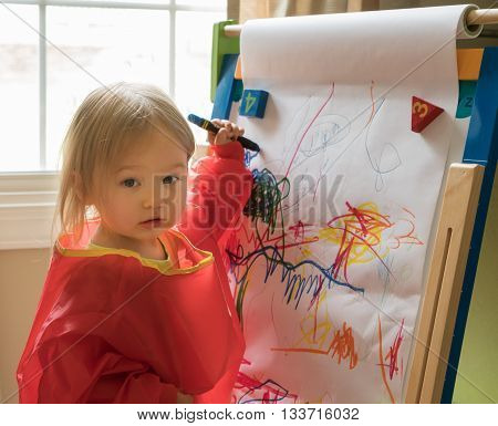Young Baby Girl Drawing At Easel