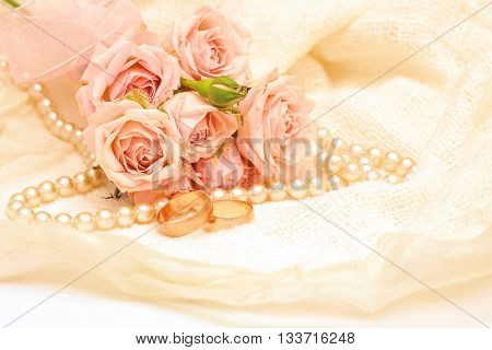 two golden rings on the background of delicate roses and pearls