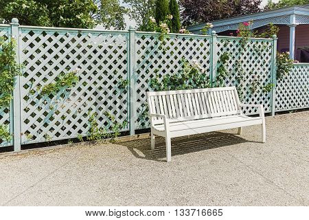 White openwork bench at the fence in the park.