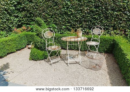 Openwork iron garden furniture to the background of the hedge.