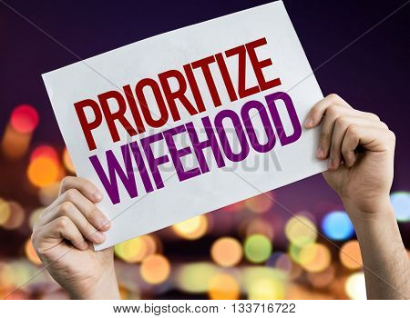 Prioritize Wifehood placard with night lights on background