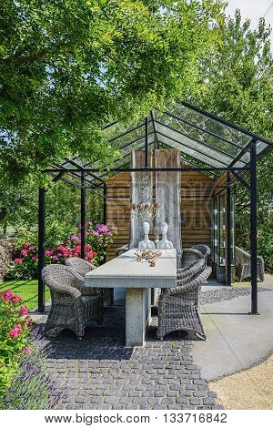 Appeltern The Netherlands July 22 2015: The Gardens of Appeltern is the inspiration garden park in the Netherlands. In this picture a greenhouse with in front two mannequins sitting at a stone table.