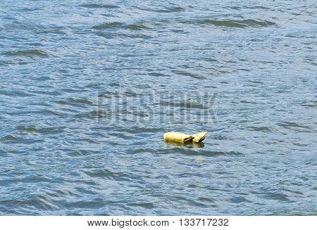 Yellow life preserver abandoned and floating down the river with nobody there