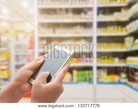 Pharmacy store Women using smart phone on blurred pharmacy store
