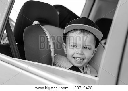 portrait happy toddler boy sitting in the car seat ( black and white )