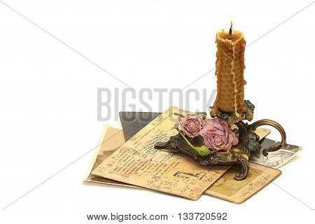 Antique bronze candlestick burning candle roses old photos and correspondence isolated on white background