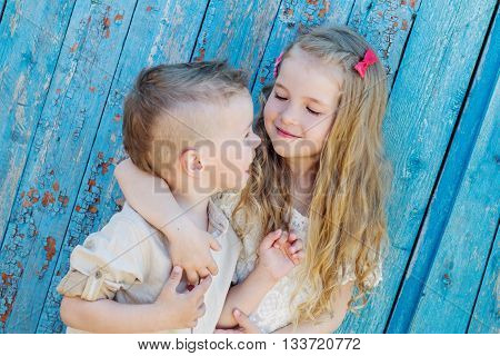Happy Toddler brother and sister hugging in summer