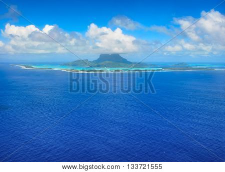 Aerial view from an airplane towards the honeymoon destination of the tropical island of Bora Bora with reef and turquoise lagoon. Bora Bora is an island near Tahiti in the tropical archipelago of French Polynesia inside the Pacific ocean.