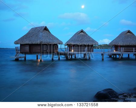 Three thatched roof overwater bungalows in a luxuous honeymoon resort in the water of the lagoon of the tropical island Bora Bora near Tahiti in pacific French Polynesia during dusk at 'blue hour'.