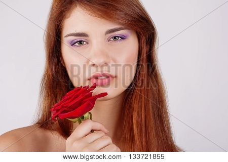 sensual teen girl holds a rose in hand on white background